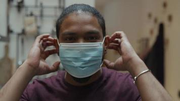 close-up do homem negro, olha para a lente da câmera, sorrindo, coloca máscara facial com as duas mãos, ajustando a máscara, olhos sorridentes video