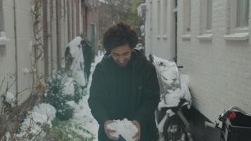 jonge man uit het Midden-Oosten in straat met sneeuw, neemt sneeuw in zijn handen, rent naar de camera en gooit sneeuw in de lucht, glimlachend in de camera video