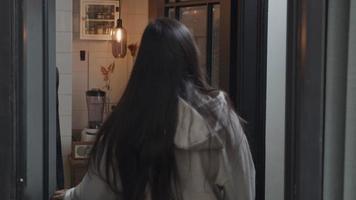 jovem mestiça caminha para o corredor, abre o armário do guarda-roupa, tira o casaco, fecha o armário da porta, veste o casaco, vai até a porta da frente