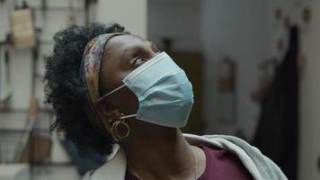 foto na cabeça de uma mulher madura negra com máscara facial, em pé no corredor, olha para cima, vira a cabeça e os olhos para a câmera, olhos olhando para a câmera
