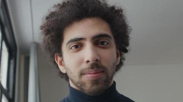 Gros plan du jeune homme du Moyen-Orient, regardant dans l'objectif de la caméra, souriant video