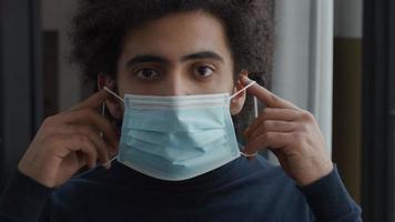 close-up de um jovem homem do Oriente Médio, olhando pelas lentes da câmera, colocando uma máscara facial, ajustando a máscara video