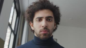 close-up de jovem homem do Oriente Médio, cabeça ligeiramente voltada para baixo, olhando seriamente para as lentes da câmera video