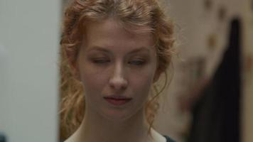 close-up de uma jovem mulher branca, olhando pela lente da câmera, piscando video