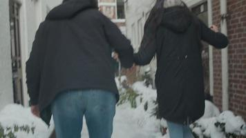 jonge man uit het Midden-Oosten en jonge vrouw van gemengd ras lopen in de sneeuw, in kleine straat, man neemt sneeuw, gooit sneeuwbal naar vrouw video