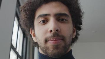 close-up de jovem homem do Oriente Médio, cabeça ligeiramente voltada para baixo, olhando, sorrindo um pouco, para a lente da câmera, olhos seguindo video