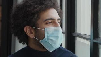 Gros plan d'un jeune homme du Moyen-Orient avec un masque facial, regarde à travers la fenêtre, lève les sourcils, les yeux et les yeux regardant droit devant video