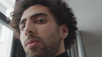close-up de um jovem homem do Oriente Médio, cabeça ligeiramente voltada para baixo, olhando seriamente para as lentes da câmera, olhos acompanhando video