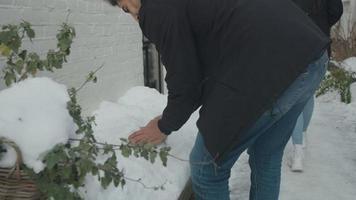 ung man från Mellanöstern och ung blandad raskvinna som går i snö, på liten gata tar mannen snö, kastar snöboll på kvinnan