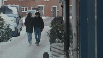 ung man från Mellanöstern och ung blandad kvinna som går i snö, på gatan, mannen lägger armen runt kvinnan, de pratar, går och skrattar