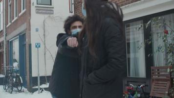 Jeune homme du Moyen-Orient rencontre une jeune femme métisse dans la rue avec de la neige, des masques, disant bonjour, toucher les coudes, continuer à marcher video