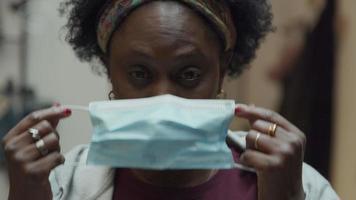 foto na cabeça de uma mulher negra madura em pé no corredor, sorrindo para a lente da câmera, colocando máscara facial, ajustando-a, olhos olhando para a câmera video