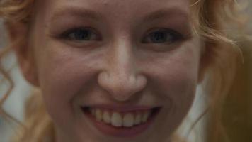 close-up extremo do rosto de uma jovem branca que ri, olhos olhando para a lente da câmera video