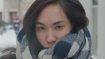 close-up de uma mulher de raça mista em pé na neve, segurando um xale de lã enrolado no pescoço, olhos olhando pela lente da câmera video