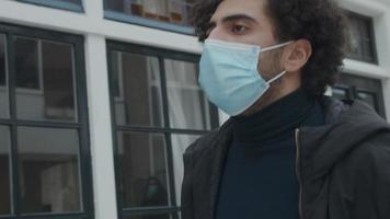 Jeune homme du Moyen-Orient avec masque facial, marche dans la rue le long des maisons video