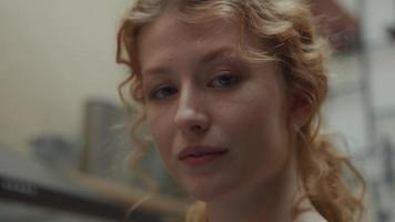 close-up de uma jovem mulher branca, em pé no corredor, os olhos seguindo a câmera em movimento ao redor do rosto video