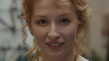 Gros plan du visage de la jeune femme blanche, les yeux regardant dans l'objectif de la caméra, la bouche ouverte, souriant de temps en temps, à la recherche intéressée video
