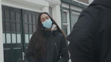 jovem mulher mestiça com máscara facial fala, na rua com neve, para jovem homem do Oriente Médio, visto de costas