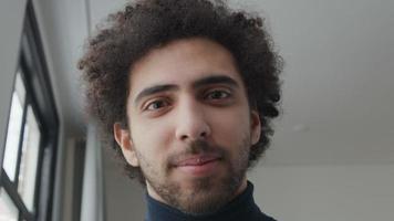 close-up de um jovem homem do Oriente Médio, cabeça ligeiramente voltada para baixo, olhando pela lente da câmera, sorrindo com a boca e os olhos, os olhos acompanhando video