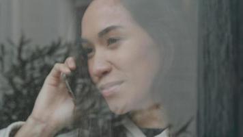 close-up de um jovem homem do Oriente Médio parado na frente da casa, chamando uma jovem mestiça, atrás da janela video