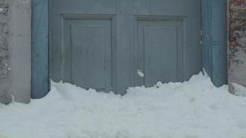 Piled up snow against lower part of front door, door frames and wall