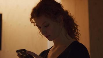 foto na cabeça de uma jovem branca segurando e digitando no celular na frente dela