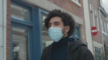 jovem homem do Oriente Médio com máscara facial, caminha na rua ao longo de casas video