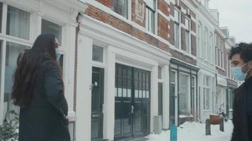 Jeune homme du Moyen-Orient rencontre une jeune femme métisse dans la rue avec de la neige, des masques, disant bonjour, toucher les coudes, parler video
