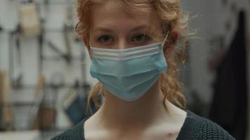 close-up van witte jonge vrouw met gezichtsmasker, ogen op zoek naar camera, hand beweegt haar op hoofd video