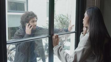 jovem homem do Oriente Médio em frente a casa chama uma jovem mestiça, que fica em frente à janela segurando o telefone na orelha