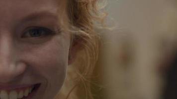close-up extremo do rosto da parte direita de uma jovem mulher branca que ri, olhos olhando para as lentes da câmera