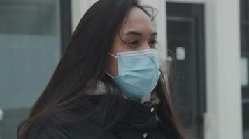 Jeune femme métisse et jeune homme du Moyen-Orient avec masque sur le visage, parler à distance dans la rue avec de la neige video