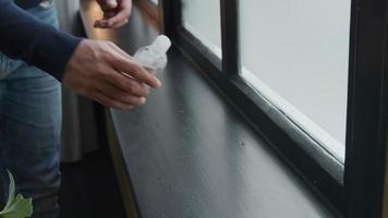 A mão de um jovem homem do Oriente Médio pega o gel do peitoril da janela, coloca o gel na palma da mão, esfrega o gel nas mãos completamente video