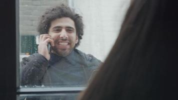jovem homem do Oriente Médio em frente a casa chama uma jovem mestiça, que fica em frente à janela