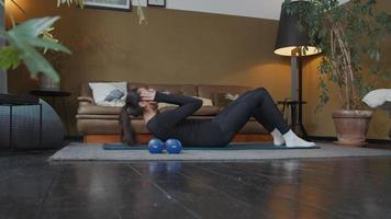 jonge gemengd ras vrouw liggend op yoga mat op tapijt voor bank, sit-ups doen in de woonkamer