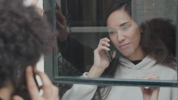 jovem mestiça em pé dentro de casa atrás da janela chamando e olhando para um jovem homem do Oriente Médio, em pé ao ar livre video