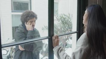 ung Mellanöstern man som står framför huset, kallar ung blandad ras kvinna, som står framför fönstret