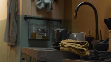 Cerca del fregadero y parte del mostrador con grifo, tazas, platillos, mortero y toalla de cocina video
