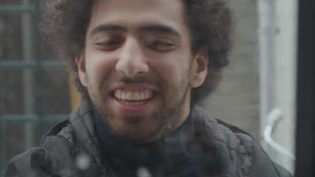 jovem homem do Oriente Médio, visto pela janela, escreve coração na janela, ri, tira neve da janela, gestos, desculpem-me video