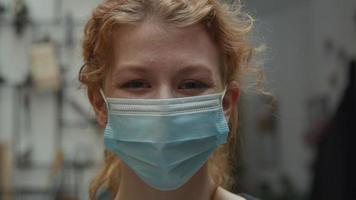 close-up de uma jovem branca com máscara facial, olhos olhando para a câmera, rindo video