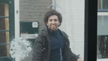 jovem homem do Oriente Médio, visto pela janela, ri e joga bolas de neve contra a janela video