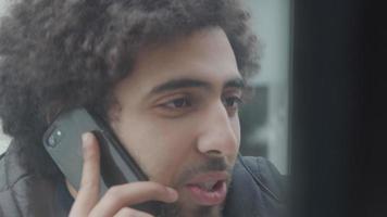 jovem homem do Oriente Médio parado do lado de fora, em frente à janela, olhando através dela, falando animadamente, segurando o telefone celular no ouvido video
