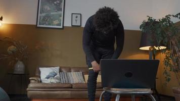 jovem homem do Oriente Médio na sala de estar ajusta a faixa de resistência acima dos joelhos