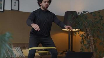 jovem homem do Oriente Médio na sala de estar, em pé, laptop na frente, agacha-se e levanta-se com faixa de resistência acima dos joelhos