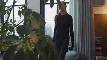 jonge vrouw van gemengd ras in de woonkamer, staande, houdt halters in haar handen, op zijn beurt gebogen benen