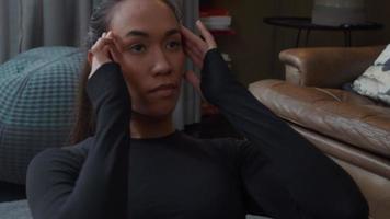 jonge vrouw van gemengd ras liggend op de vloer van de woonkamer, sit-ups doen