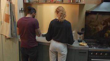 homem negro e jovem branca na cozinha na pia, conversando, mulher lavando pratos, olhando em volta, homem limpa a louça, dá um passo para trás