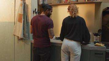 svart man och ung vit kvinna i köket vid handfat, prata, kvinna diska, mannen håller kökshandduk