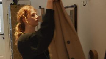 ung vit kvinna, går nerför trappan i korridoren, tar kappa från kappkroken, tar på sig kappan, ser in i spegeln, justerar håret, vänder