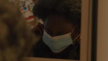 Spiegel mit schwarzer reifer Frau, die hinein schaut, setzt Gesichtsmaske auf, stellt sie ein, dreht sich, während sie in Spiegel schaut, Blätter video